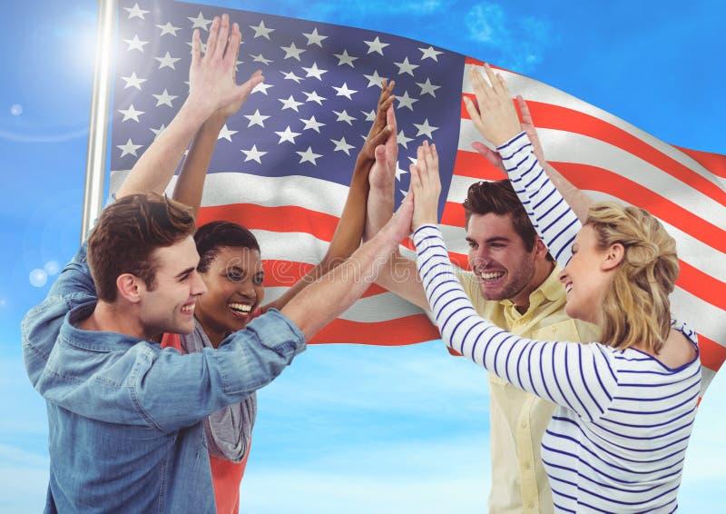 Le vänner som upp kastar deras händer mot att fladdra amerikanska flagganbakgrund arkivfoton