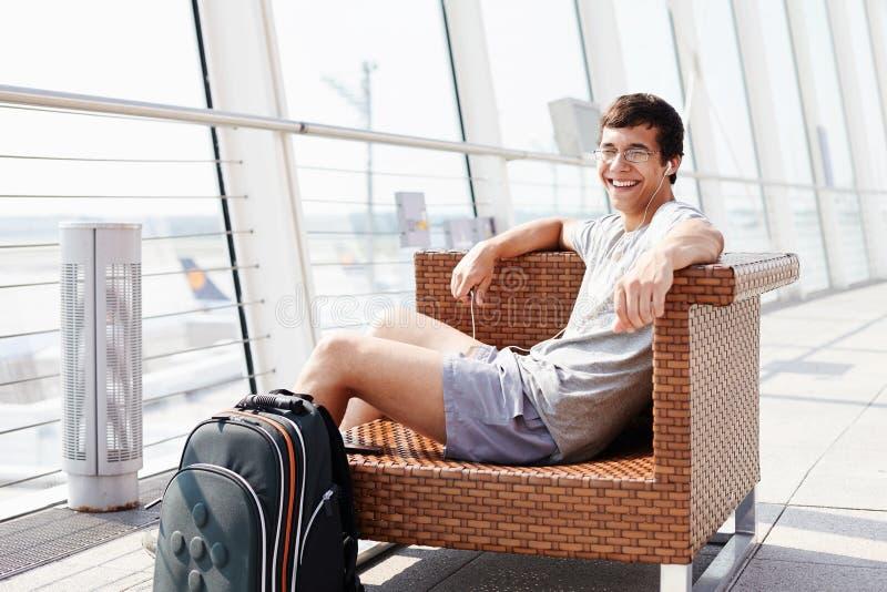 Le väntande på flyg för man på flygplatsen royaltyfria foton