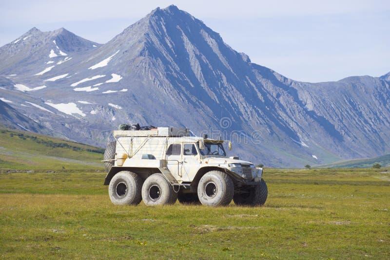 Le véhicule tout-terrain de Trekol dans la perspective des montagnes d'Ural polaire images stock