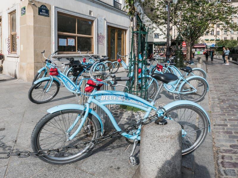 Le vélo bleu voyage la librairie extérieure garée par bicyclettes à Paris photos libres de droits