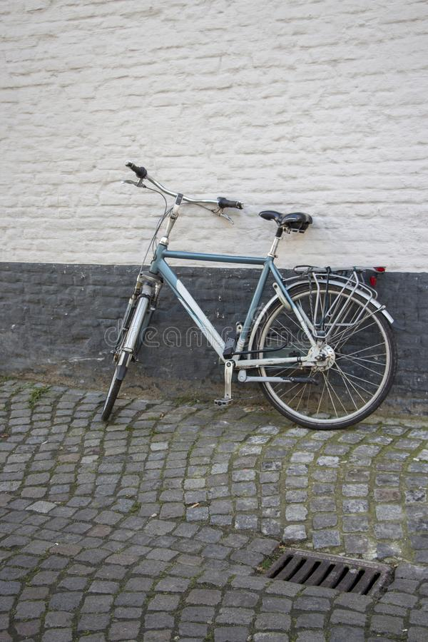 Le vélo s'est penché contre dessus un mur gris-foncé et blanc photo stock
