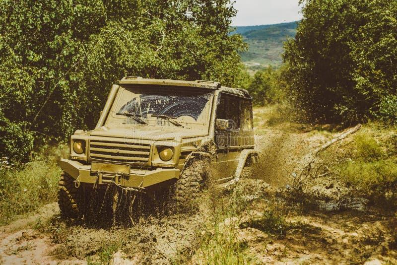 Le v?hicule tous terrains va sur le chemin de montagne Pneus en vue de course De jeep aventures dehors Suv de safari Mudding est photographie stock libre de droits
