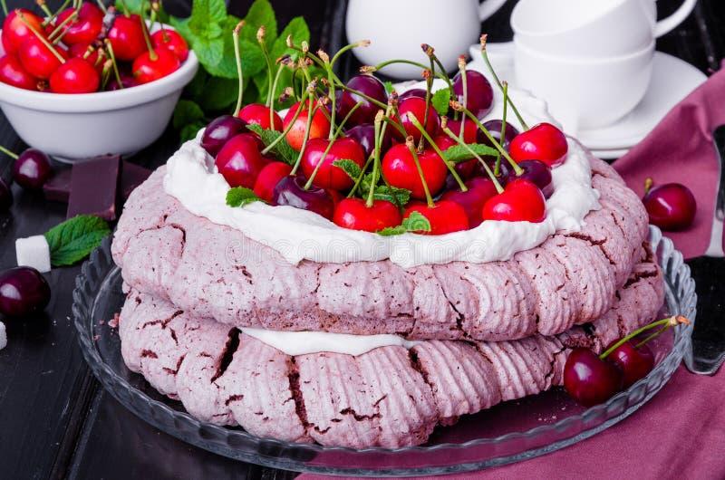 Le vacherin de chocolat durcit avec de la crème et les cerises fouettées photo libre de droits