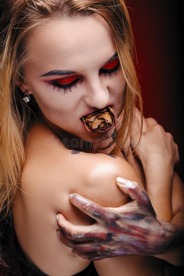 Le vampire de fille de Halloween avec le rouge observe les lèvres rouges et le fond rouge photographie stock
