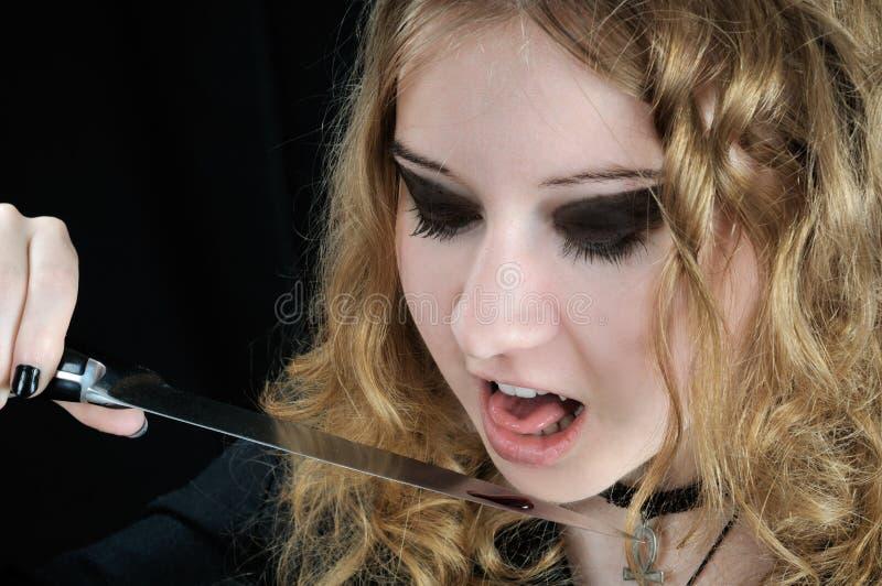 Le vampire veut lécher la baisse de sang du couteau image libre de droits