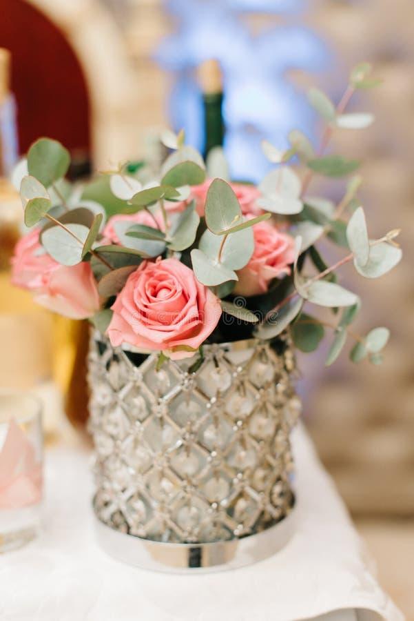 Le vase en verre magnifique tient les roses en pastel roses image libre de droits