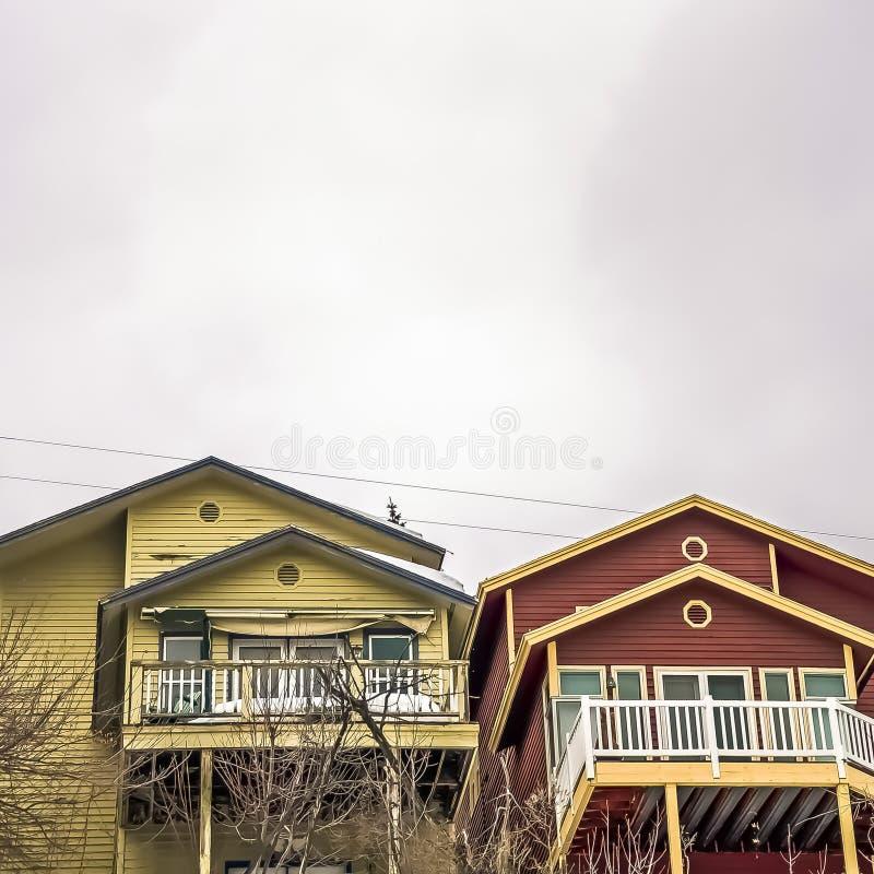 Le vaste ciel nuageux de place au-dessus des maisons colorées et la neige ont couvert la terre en hiver photos libres de droits
