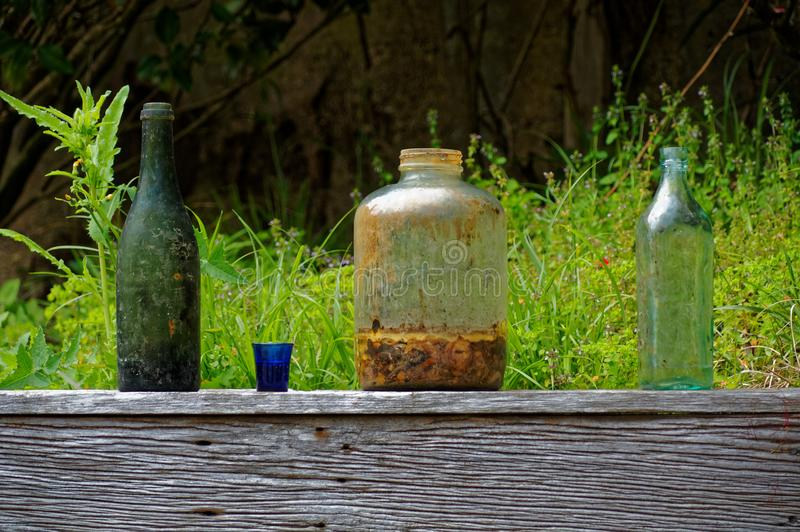 Le vecchi bottiglie e barattoli hanno scartato su un recinto di legno del giardino fotografia stock libera da diritti
