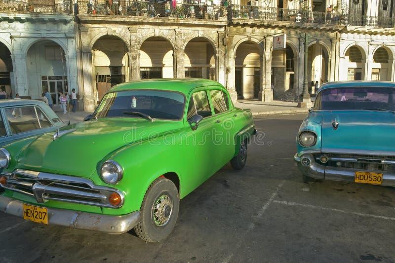 Le vecchie automobili americane del turchese e di verde sono parcheggiate davanti alle vecchie costruzioni a vecchia Avana, Cuba immagini stock libere da diritti