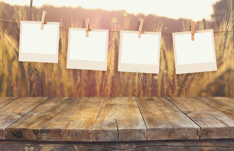 Le vecchie strutture della foto della polaroid che appendono su una corda con la tavola d'annata del bordo di legno davanti al gi immagini stock