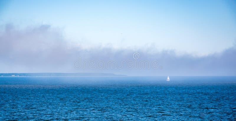 Le vele dell'yacht sul mare aperto nella nebbia Navigazione un giorno nebbioso yachts Barca a vela immagini stock