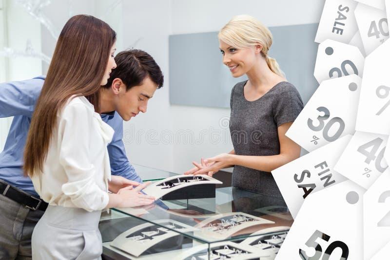 Le vendeur aide des couples pour sélectionner des bijoux en vente photos stock