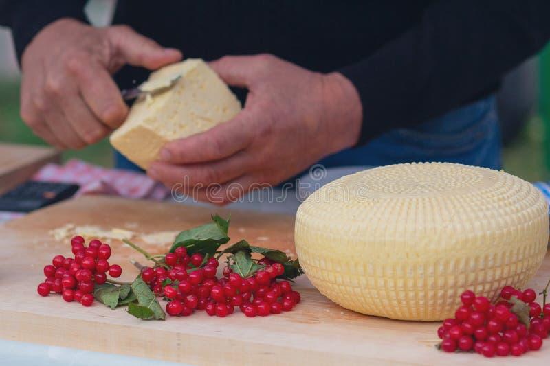 Le vendeur coupe et vend le fromage photos stock