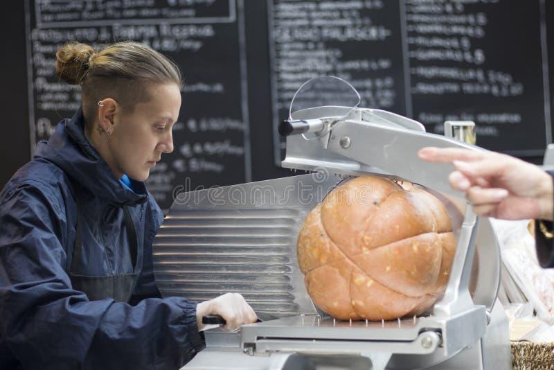 Le vendeur coupe le jamon sur le marché de ville photos stock