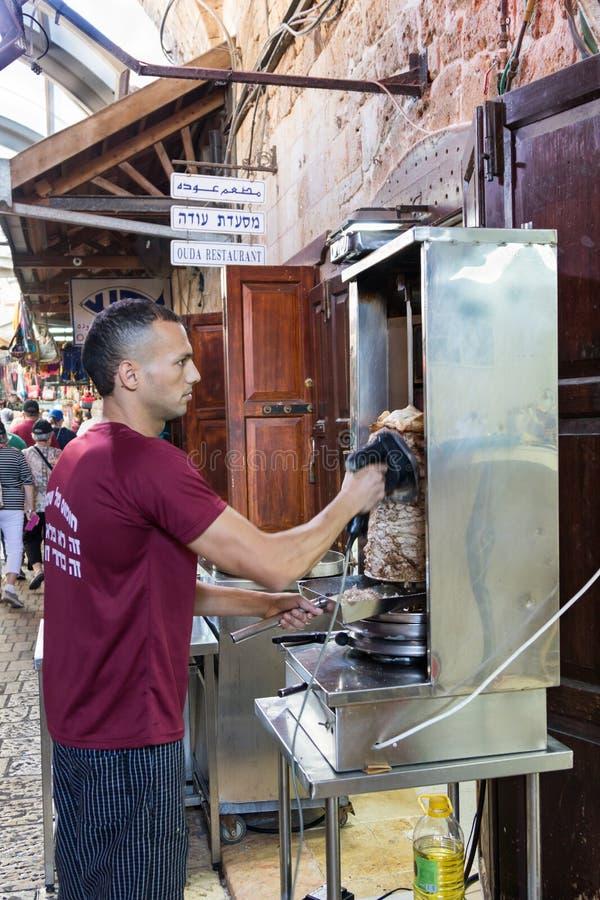 Le vendeur coupe le shawarma électrique du gril pour des clients sur le marché de la vieille ville de l'acre en Israël images libres de droits