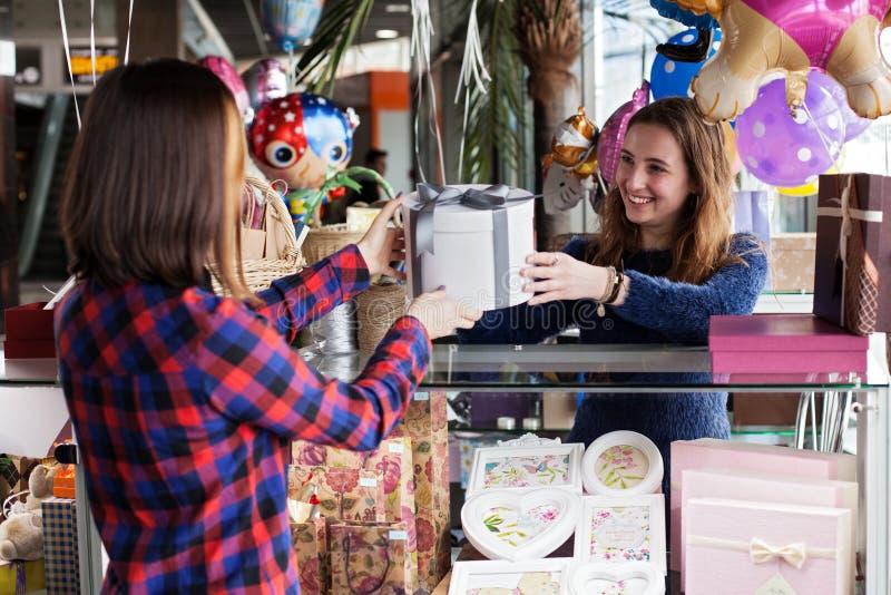 Le vendeur de cadeau de femme donne la boîte photographie stock