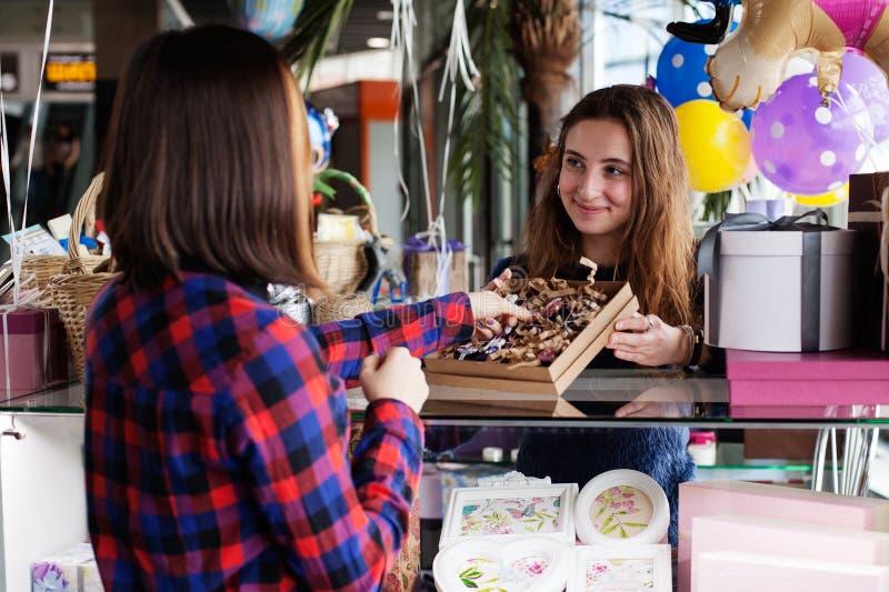 Le vendeur de cadeau de femme montre les marchandises photographie stock