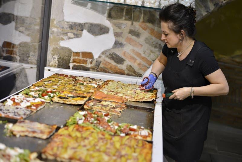Le vendeur de la pizzeria coupe la pizza avec des ciseaux images stock