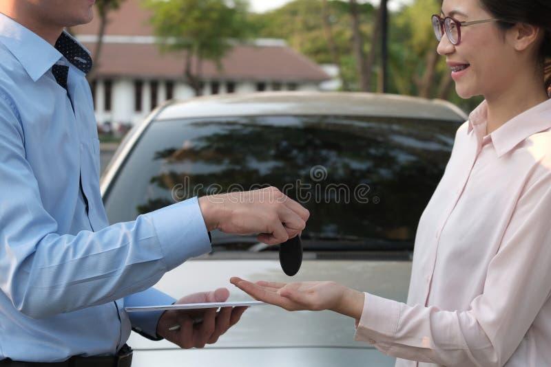 Le vendeur donnent la clé de voiture au client voiture de achat de femme de revendeur images libres de droits