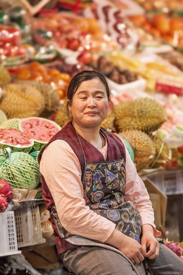 Le vendeur féminin fatigué vend le fruit sur un marché d'intérieur local, Pékin, Chine images stock