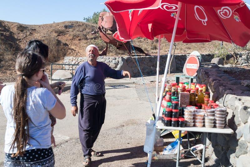 Le vendeur - le druz se tient avec le client et offre les marchandises, près de sa boutique avec les bonbons en boîte dans le par photo libre de droits