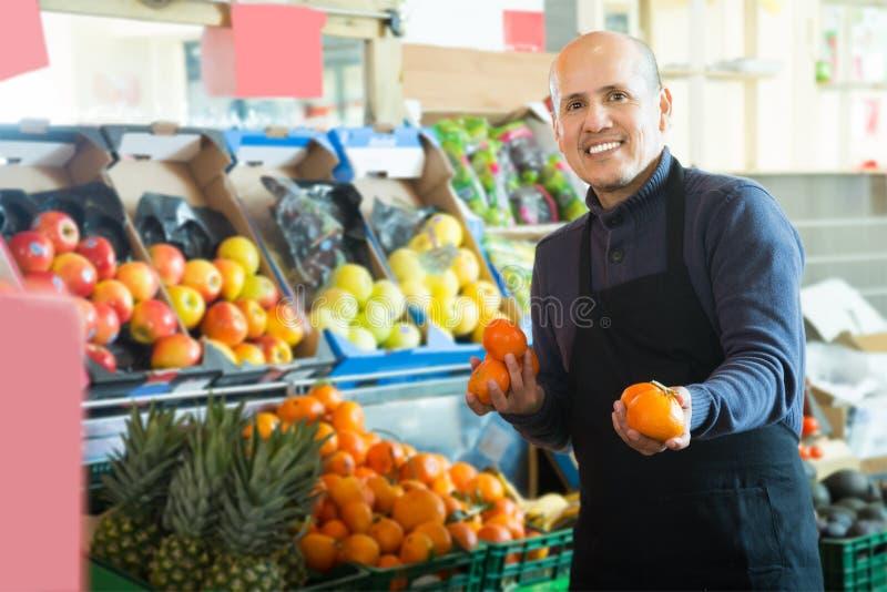 Le vendeur masculin mûr offre des mandarines image libre de droits