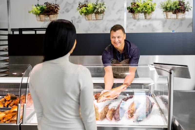 Le vendeur montrant des fruits de mer au client aux poissons font des emplettes photo libre de droits
