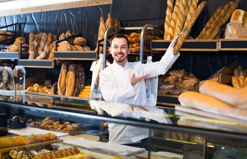 Le vendeur montre une sélection des baguettes françaises photo stock