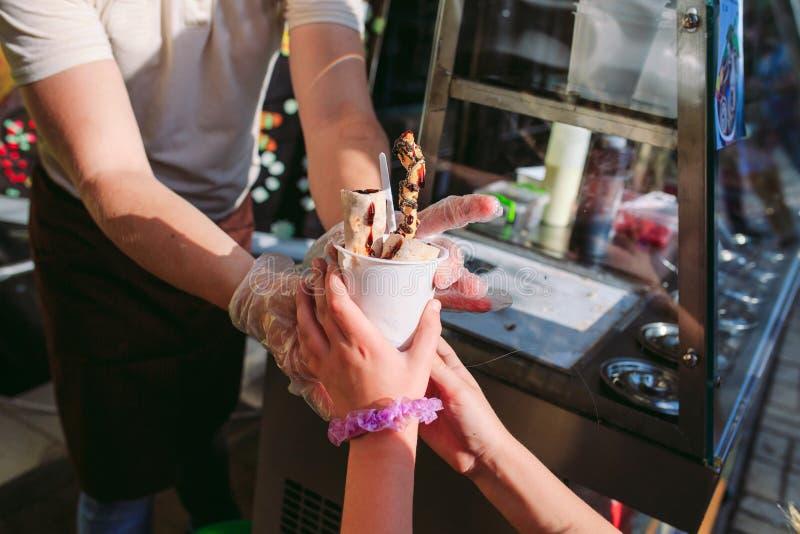 Le vendeur passe la crème glacée à une petite fille La cr?me glac?e faite sauter ? feu vif roule ? la casserole de gel Glace roul images stock