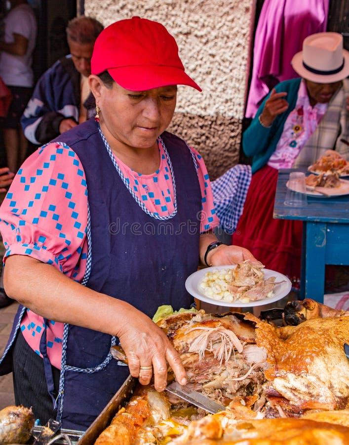 Le vendeur prépare le déjeuner de porc de Hornado pour le client images libres de droits