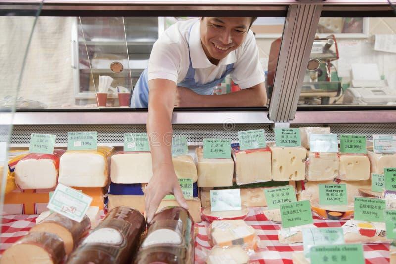 Le vendite Clerk il raggiungimento dentro per ottenere il formaggio alla ghiottoneria contro fotografia stock libera da diritti