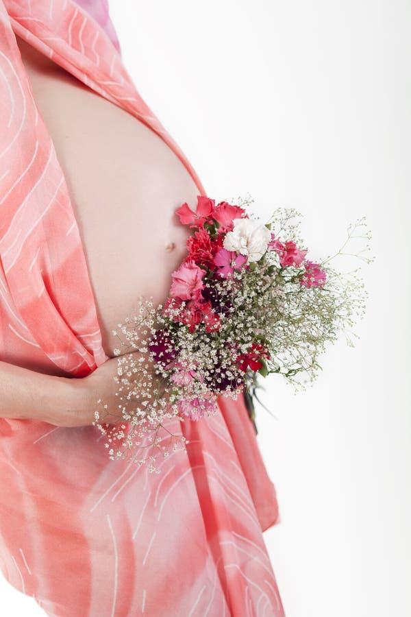 Le ventre de femme enceinte avec des fleurs photographie stock