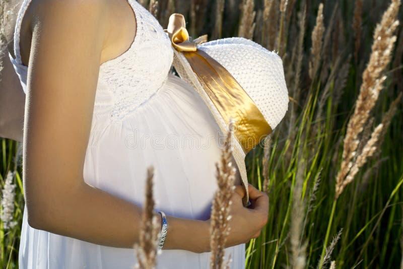 Le ventre de femme enceinte avec le chapeau dans les rayons de soleil images stock