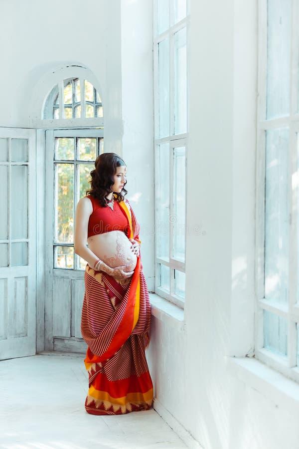 Le ventre de femme enceinte avec le tatouage de henné photos stock