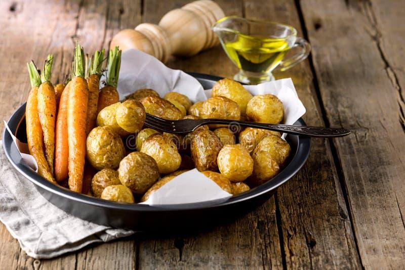 Le verdure cotte hanno grigliato le carote e le verdure delle patate hanno cucinato sull'alimento di legno di dieta sana del fond immagini stock
