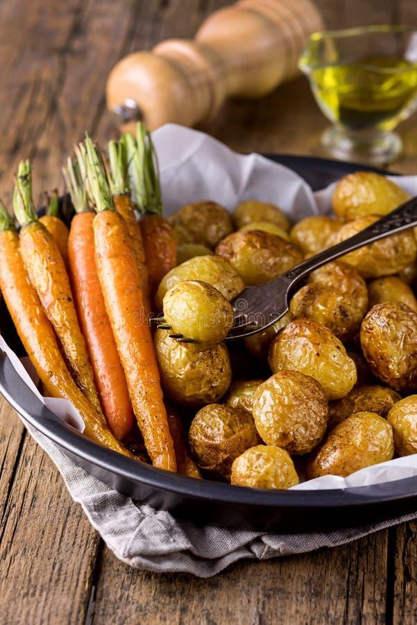 Le verdure cotte hanno grigliato le carote e le verdure delle patate hanno cucinato sull'alimento di legno di dieta sana del fond immagine stock libera da diritti