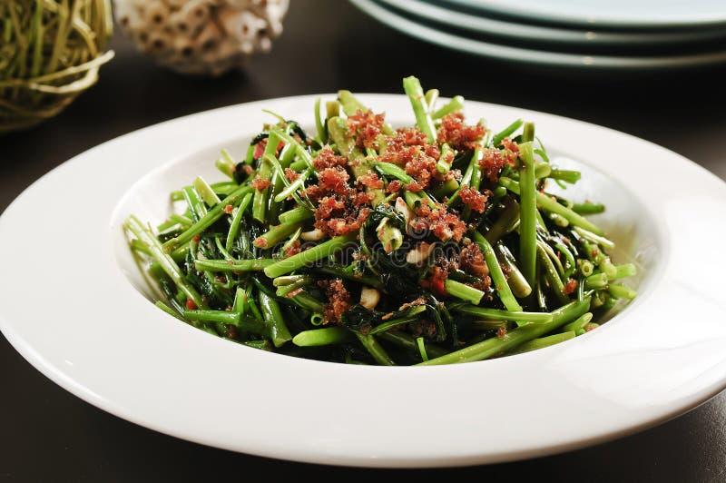 Le verdure fritte del muong di rau o di ipomea su bianco plat fotografie stock libere da diritti
