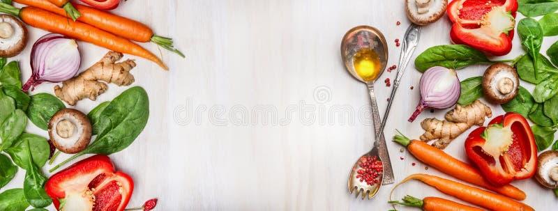 Le verdure pulite organiche hanno ordinato con la cottura i cucchiai e dell'olio su fondo di legno bianco, la vista superiore, in fotografia stock