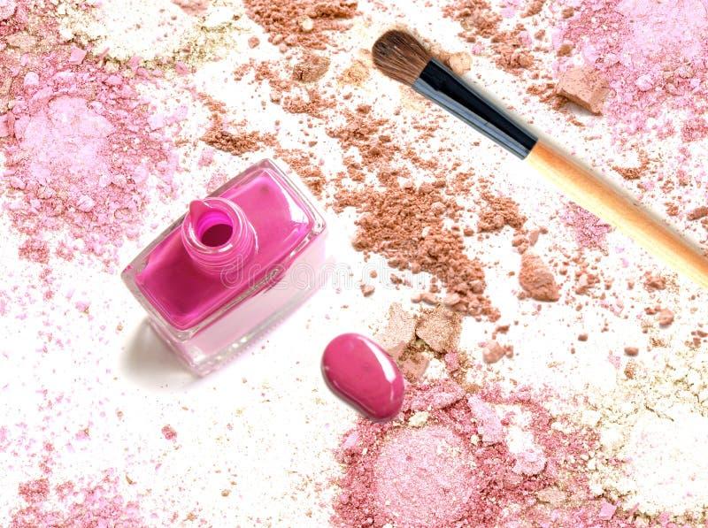Le vernis à ongles rose sur la poudre rose écrasée composent image libre de droits