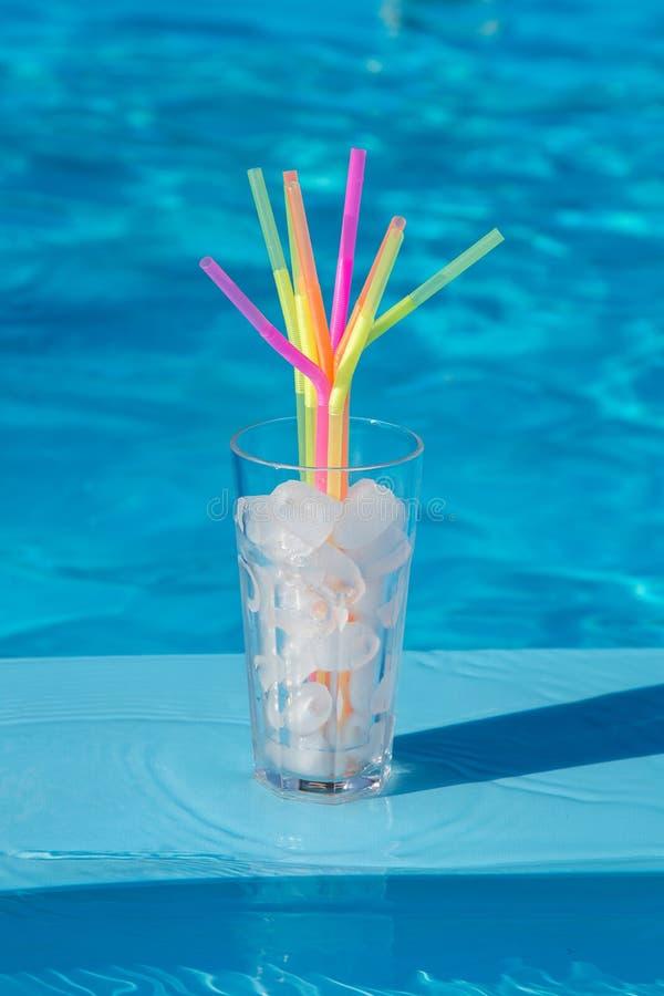 Le verre avec de la glace et les pailles glacent près de la piscine photo stock