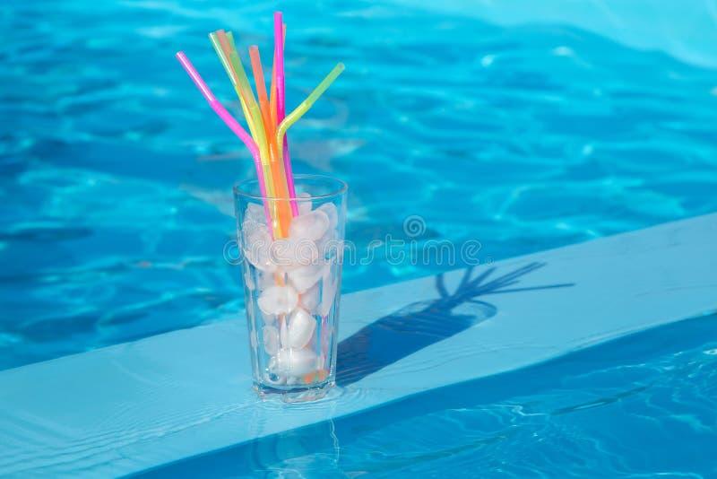 Le verre avec de la glace et les pailles glacent près de la piscine photos stock