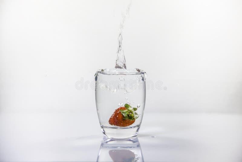 Le verre d'eau douce avec la fraise a plongé en causant une éclaboussure photo stock