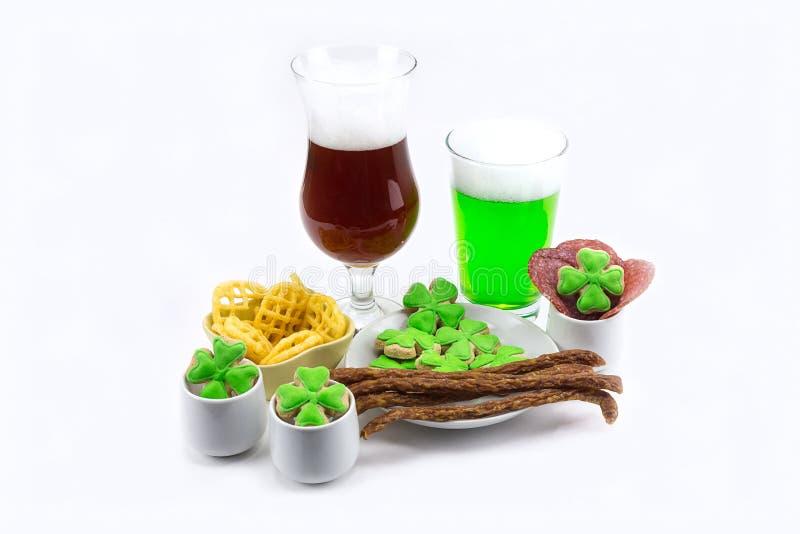 Le verre de bière de jour du ` s de StPatrick du plat vert de trèfle avec de la viande d'apéritifs ébrèche sur le fond blanc photo stock