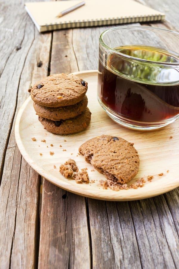 Le verre de café noir avec des gâteaux aux pépites de chocolat sur en bois plat images stock