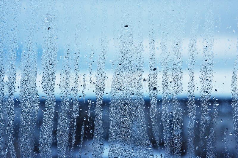Le verre de fenêtre dans le condensat dans les courants froids de l'eau laisse tomber le fond photographie stock