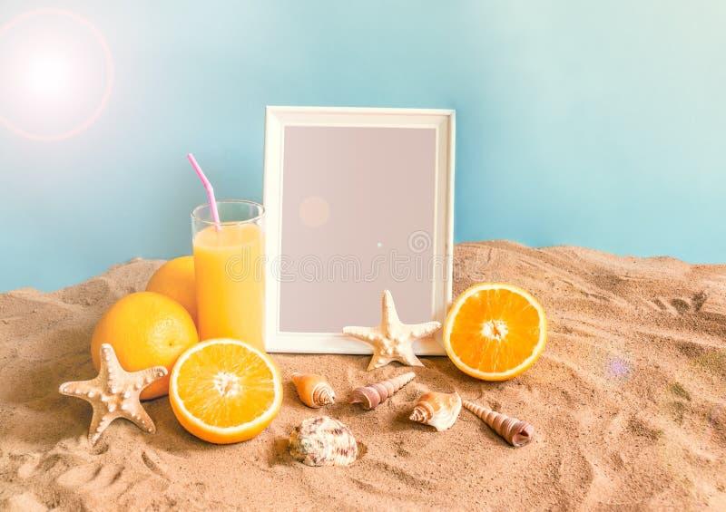 Le verre de jus d'orange, le cadre, les étoiles de mer et les coquillages sur le sable échouent photos libres de droits
