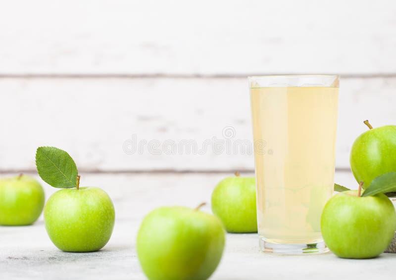 Le verre de jus de pomme organique frais avec le forgeron de mamie et les pommes des anglais Bramley dans la boîte sur le fond en photo stock