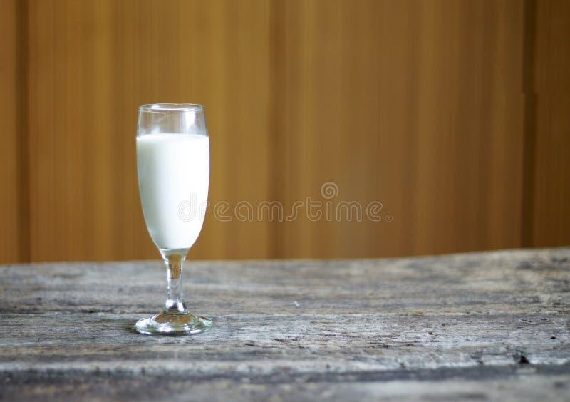 Le verre de lait a plac? sur un fond en bois photos stock