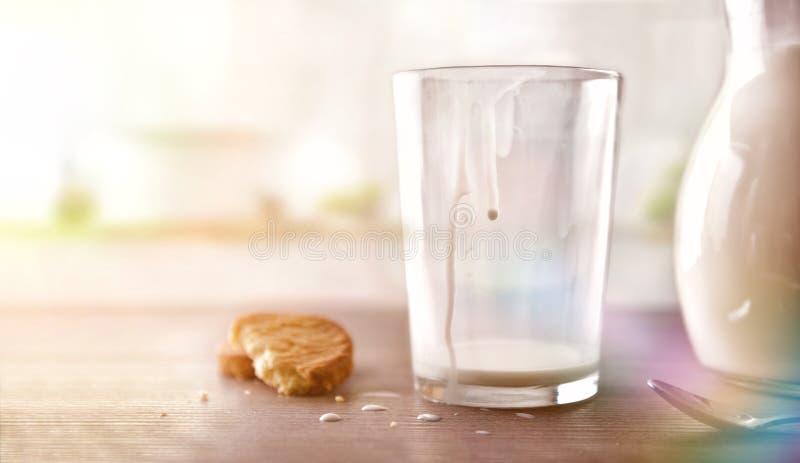 Le verre de lait pour le petit déjeuner a fini de boire dans la cuisine blanche image libre de droits