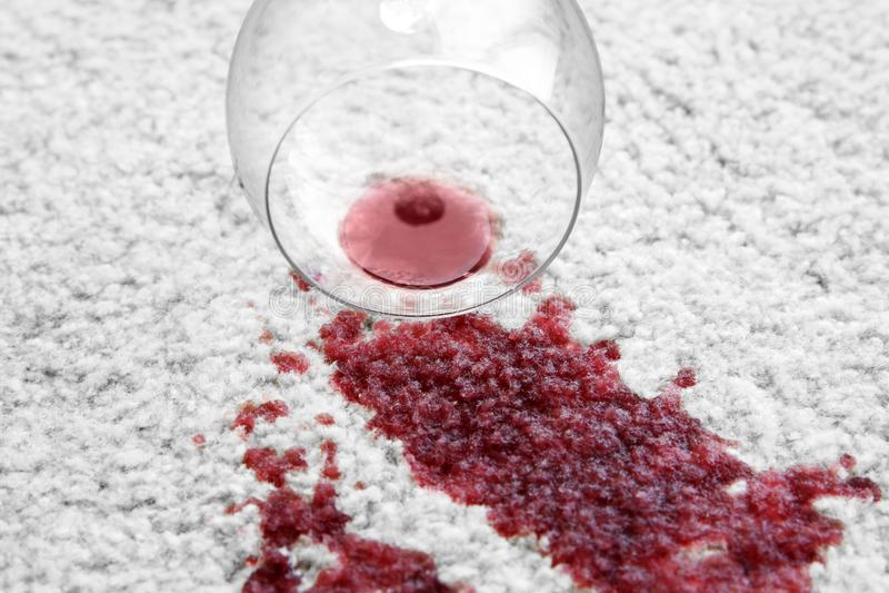 Le verre de vin rouge s'est renversé sur le tapis blanc, image stock